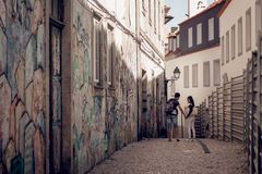 Lovely couple walking in narrow street with graffiti stock images