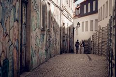 Lovely couple walking in narrow street with graffiti stock photos