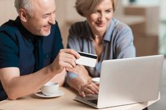 Lovely couple wanting to buy something online and pay. With credit card Royalty Free Stock Photography