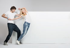 Lovely couple with white board in the background Stock Photography