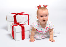 Lovely crying baby. Girl with two gift boxes over white background Royalty Free Stock Image