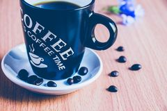 A lovely cup of coffee and some coffee beans. On the brown wooden table floor for background Royalty Free Stock Image