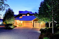 Lovely curb appeal of large luxury house with blue roof. Summer evening stock image