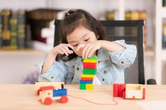 Lovely cute little Asian girl in jeans shirt playing wood block. Toys on desk. Concept for funny activity of young kids in free time stock images