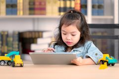 Lovely cute little Asian girl in jeans shirtdrawing on desk. Co stock image