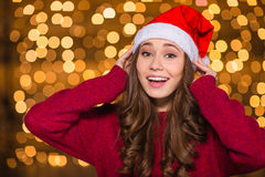 Lovely cute smiling female in santa claus hat Stock Photos