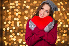 Lovely cute young woman hugging red heart over shiny background Stock Images
