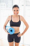 Lovely dark haired model in sportswear carrying a blue exercise mat Royalty Free Stock Image