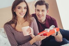 Portrait of happy couple with a present. Lovely date. Portrait of young charming couple looking at you with amusement while holding a splendid present and stock photos