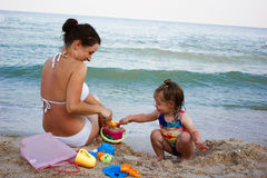 Lovely daughter plays happily with her mother. On the beach, there is a sand castle royalty free stock photography
