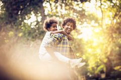 Lovely day with father. African American father and daughter playing in park. Carrying on piggyback royalty free stock photo