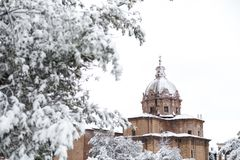 A lovely day of snow in Rome, Italy, 26th February 2018: a beautiful view of snowy Roman Forums and Church of the Saints Luca and. Martina under the snow royalty free stock image