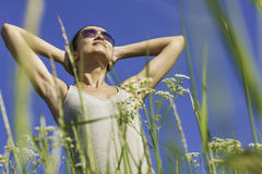 Lovely Day. Young woman pausing to feel sun on face Stock Image