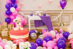 Beautifully decorated children`s party with balloons flowers and sweets. A lovely delicious candy bar in pink and purple colors for a little princess on her 1st Stock Photos
