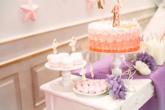 Beautifully decorated children`s party with balloons flowers and sweets. A lovely delicious candy bar in pink and purple colors for a little princess on her 1st Royalty Free Stock Images