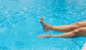 Lovely, delightful, female feet, water splashes and turquoise pool water royalty free stock image