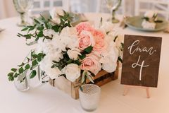 Lovely details decoration of a beautiful and stylish wedding: flowers in a wooden box and number of a table royalty free stock photography