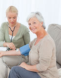 Lovely doctor taking the blood pressure Stock Image