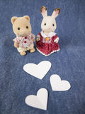 Lovely dolls with hearts. A couple of dolls and paper heart on denim fabric Stock Photography