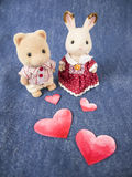 Lovely dolls with hearts. A couple of dolls with red painted paper hearts on denim fabric Stock Images
