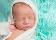 Lovely dreamy newborn boy in romper with hat, close up Royalty Free Stock Photography