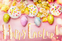 Lovely Easter setting in pastel color with decoration eggs, flowers,cakes and bokeh lighting on pink pale background, top view Stock Images