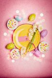 Lovely Easter setting in pastel color with decoration eggs, flowers,cakes and bokeh lighting on pink pale background, top view Stock Photography