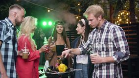 Lovely elated young people standing near grill with cooked vegetables and clinking bottles with non-alcoholic drinks. Company of smiling stylish youth having fun stock footage