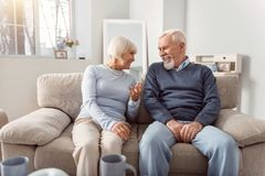Lovely elderly couple joking around while sitting on couch Stock Photography