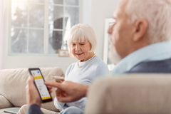 Lovely elderly couple using mobile applications on their gadgets. Useful technologies. Pleasant elderly couple sitting in the living room and being focused on stock photos