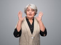 Scared senior lady looking at camera. Lovely elderly woman in elegant outfit gesturing with hands and looking at camera with terrified face expression while stock photos