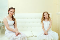 Lovely elegant sisters sitting on white couch Royalty Free Stock Photography