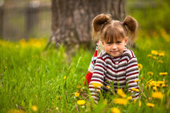 Lovely emotional girl sitting in grass. Stock Images