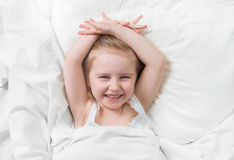 Lovely emotions of daughter smiling in bed. Lovely emotions of a daughter smiling widely, happily, awake in her white little bed royalty free stock photos