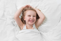 Lovely emotions of daughter smiling in bed. Lovely emotions of a daughter smiling widely, happily, awake in her white little bed royalty free stock images