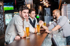 Lovely evening. Three friends men drinking beer and having fun t Royalty Free Stock Photos