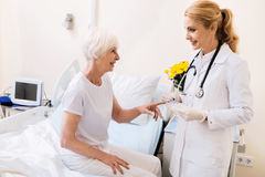 Lovely experienced doctor bringing her patient new pills Royalty Free Stock Photo