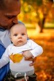 Lovely family in autumn park - baby boy enjoying with his father. Lovely family in autumn park - baby boy enjoying with his happy father stock photo