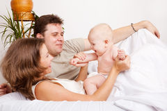 Lovely family in bed. Lovely happy family in the bedroom Stock Photo