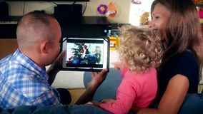 Lovely family child father and mother watch family video movie on tablet stock video