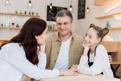 Beautiful family in cafe. Lovely family embracing in cafe and looking at each other stock photos