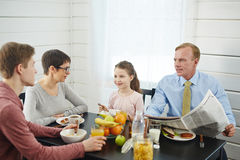 Lovely Family Enjoying Breakfast. Peaceful breakfast in bosom of family: red-haired father with newspaper in hands talking to his teenage son, little daughter stock photos