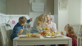 Lovely family enjoying meal in domestic kitchen. Happy lovely family with two adorable preadolescent siblings enjoying meal in domestic kitchen. Carefree family stock footage