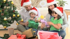 Lovely family opening Christmas gifts stock video