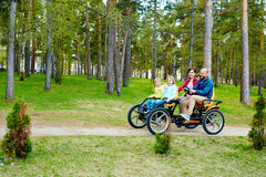 Lovely family riding quadricycle pedal car. Cheerful family of four riding orange quadricycle pedal car while enjoying spring in park with pine forests Stock Images