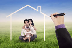Lovely family sitting under a dream house. Little happy asian family sitting on the meadow while smiling at the camera under a dream home Royalty Free Stock Image