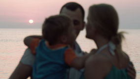 Lovely family of three together by the sea. Close-knit family of three on the beach. Father holding son, they come closer to each other. Boy kissing his parents stock video footage
