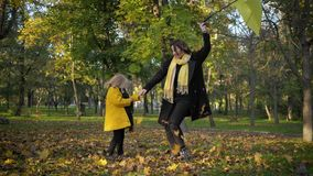 Lovely family, young mother with cheerful little daughter, having fun playing in autumn leaves with an umbrella, walking
