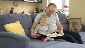 Lovely father reading story book with his baby at home. stock footage
