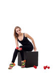 Lovely female athlete posing sitting on cube Royalty Free Stock Photo